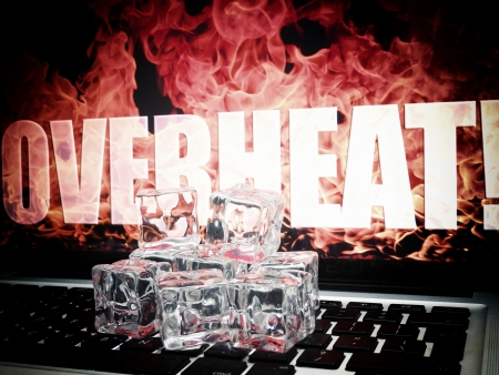 overheating: Ice cubes on computer keyboard with flames on background OVERHEAT