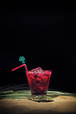 Raspberry cocktail on the sand over black background photo