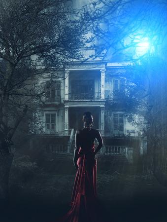 Blonde vrouw in rode jurk op spookhuis Stockfoto