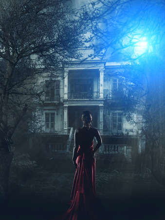 Blonde Woman in red dress at haunted house Stock Photo
