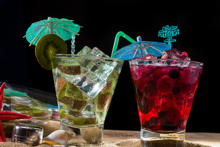Raspberry and kiwi cocktails on the sand over black background photo