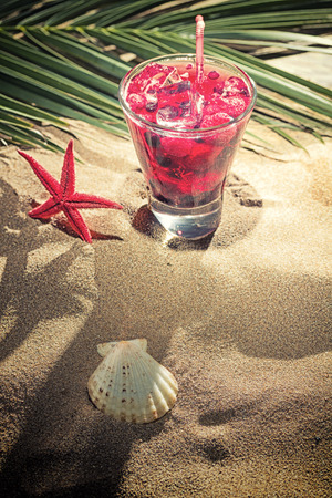 Raspberry cocktail on the sand on the beach photo