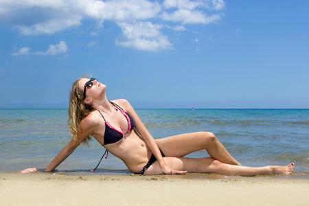 Beautiful young woman in bikini on the beach in Spain photo