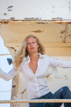 Young blonde woman in blue jeans  posing at shipwreck