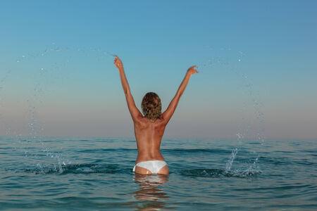 topless: Sexy jeune femme posant topless sur la plage au coucher du soleil Banque d'images