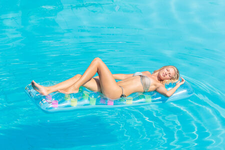 lilo: Young woman in bikini on a lilo in the swimming pool Stock Photo