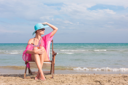 WOman sitting on a chair on the beach photo