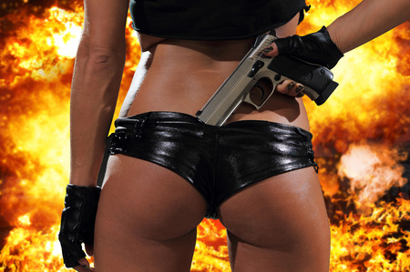 Hot blonde woman with gun over exploding background Stock Photo