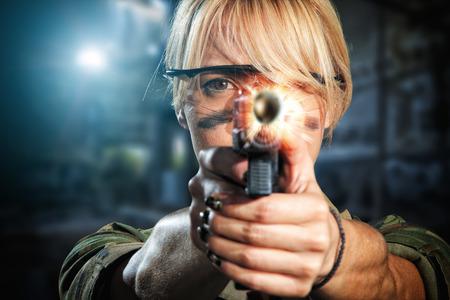 Beautiful sexy blonde girl with gun shooting photo