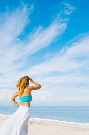 beach babe: Outdoor summer portrait of young pretty woman looking to the ocean at tropical beach, Stock Photo
