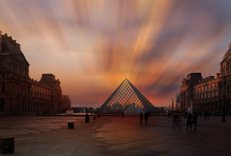 PARIS, FRANCE - DECEMBER 8, 2017: View of famous Louvre Museum with Louvre Pyramid at evening. Louvre Museum is one of the largest and most visited museums worldwide Editorial
