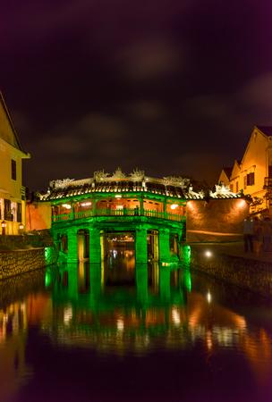iluminado a contraluz: Old Japanese bridge in the night lights. Historical landmark of the city Hoi An, Vietnam