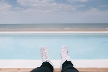 Guy chilling laying beside pool and look at sea and beach. Close up on legs and shoes.