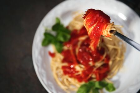 Tasty appetizing classic italian spaghetti pasta with tomato sauce, cheese parmesan and basil on plate on dark table Banco de Imagens