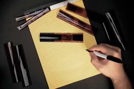 yellow notebook for planning photographs on a black background