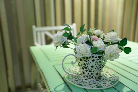 natural love: White roses in white vase on wooden dining table Stock Photo