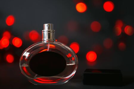 Perfume bottle on a black background with red lights. Red bokeh. holiday. Mother's day. Gift to a woman