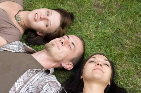 friends together relaxing on grass photo