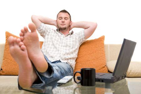 Casual Mann sitzt auf Sofa mit Laptop