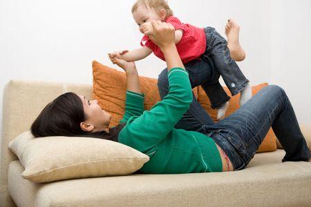 familia jugando: familia feliz jugando en sofa  Foto de archivo