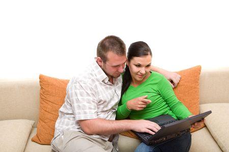 glückliches Paar Sitzung vom Sofa mit Laptop