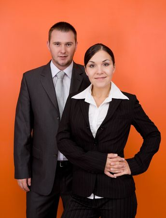 woman and man in team standing on orange background Stock Photo