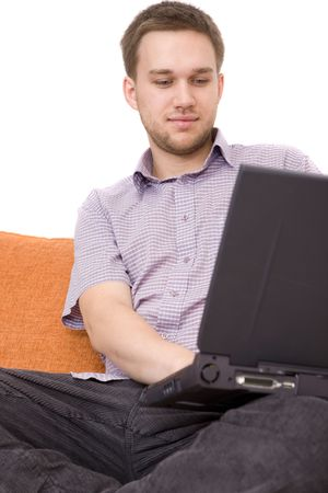 casual guy sitting on sofa with laptop Standard-Bild