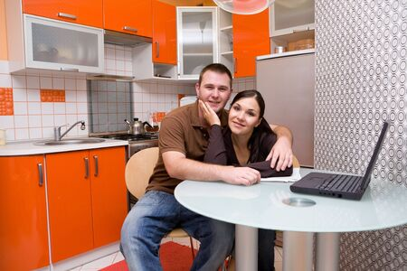 casual couple with laptop in modern kitchen photo