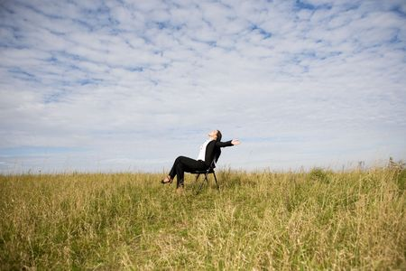 attractive brunette businesswoman relaxing on meadow photo