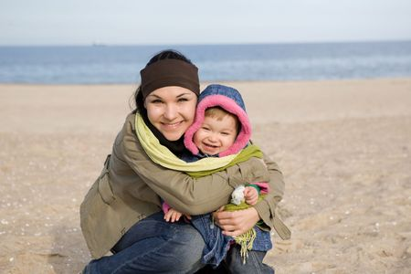 mother and daughter together on the beach photo