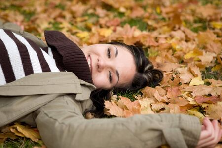 attractive brunette woman lying on leaves photo