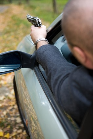gangster with gun: angry man with gun driving car Stock Photo