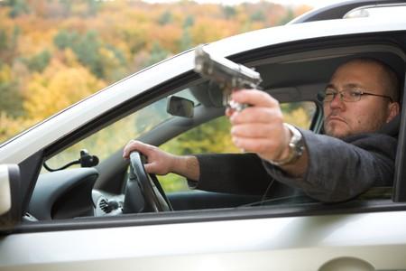 aiming: angry man with gun driving car Stock Photo