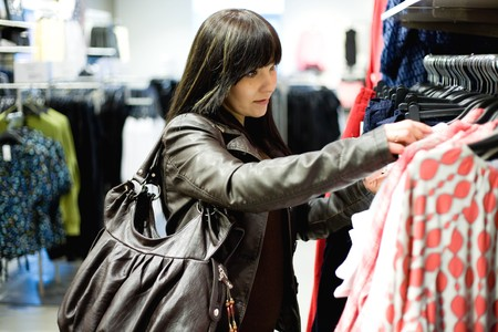 casual woman watching clothes in store Stock Photo