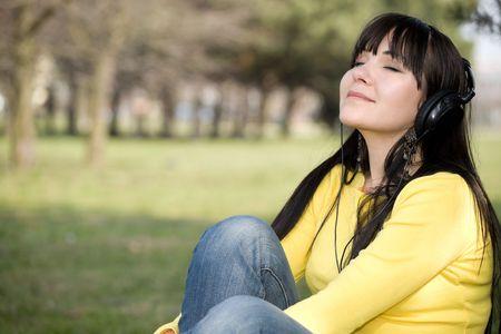 happy brunette woman with headphones relaxing in park 版權商用圖片