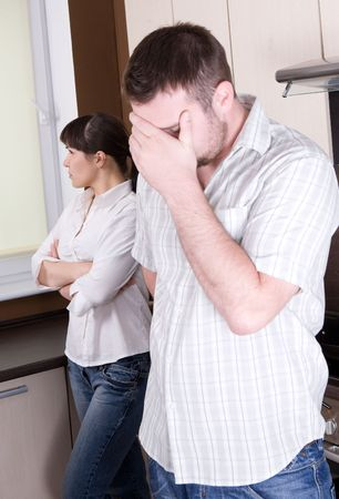 people arguing: angry couple with problems in kitchen
