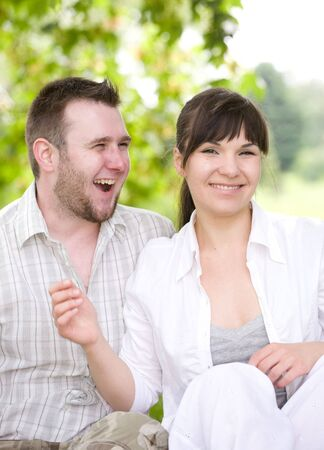 happy couple together sitting on grass photo