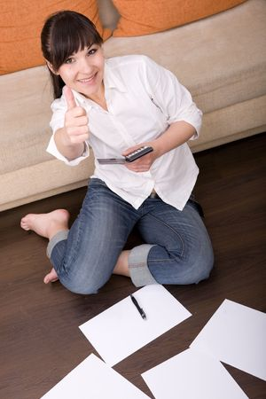 attractive brunette woman with calculator at home photo