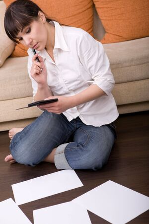 attractive brunette woman with calculator at home Stock Photo - 5064506