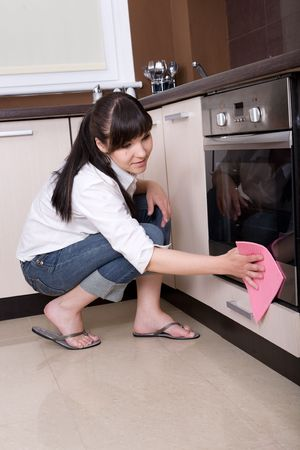 messy kitchen: young brunette woman cleaning kitchen Stock Photo