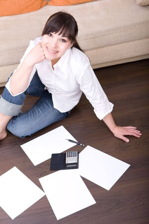 happy young woman with calculator at home photo