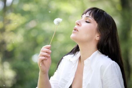 attractive brunette woman with dandelion in park photo