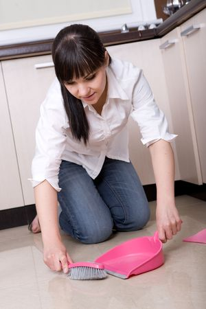 young brunette woman cleaning kitchen photo