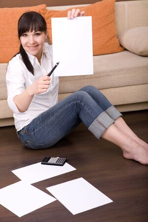 young brunette woman sitting at home with calculator photo