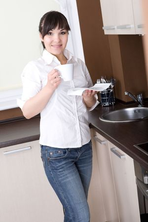 house ware: happy young woman having break in kitchen