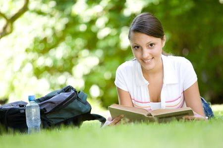 happy young woman learning in park