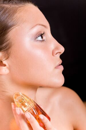 beautiful young woman with perfume photo