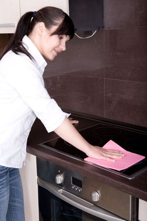 attractive young woman cleaning kitchen Standard-Bild