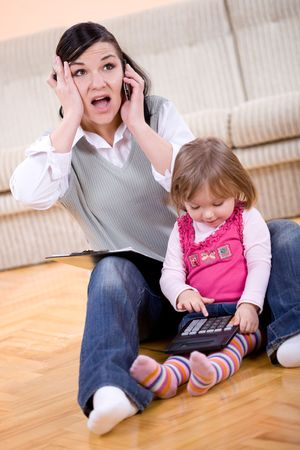 child stress: mother working at home with daughter Stock Photo