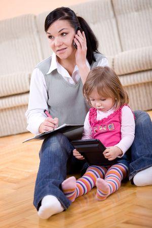 madre trabajadora: madre que trabaja en casa con la hija de Foto de archivo